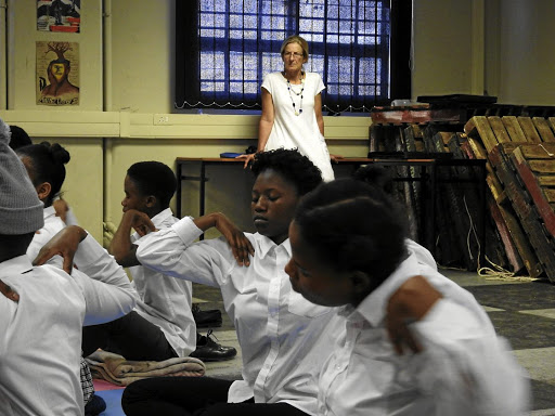 Sound of silence: Pupils at Alexandra High  School in Johannesburg go through their yoga paces under the watchful eye of instructor and founder of Yoga4Alex, Dr Marianne Felix. Picture: LESLEY STONES