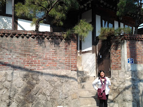 Photo: Mama Chelle in front of one of the traditional houses in Bukchon Hanok Village.
