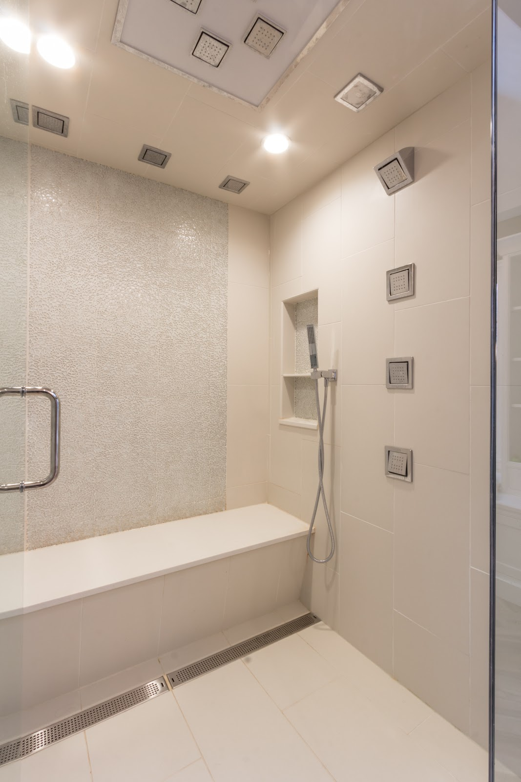 Large steam shower with wall and ceiling shower heads, lounge bench and vents.