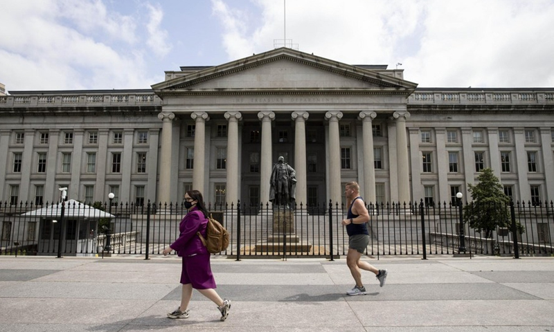 People walk past the US Treasury Department building in Washington, D.C., the United States, May 21, 2020. (Photo by Ting Shen/Xinhua)