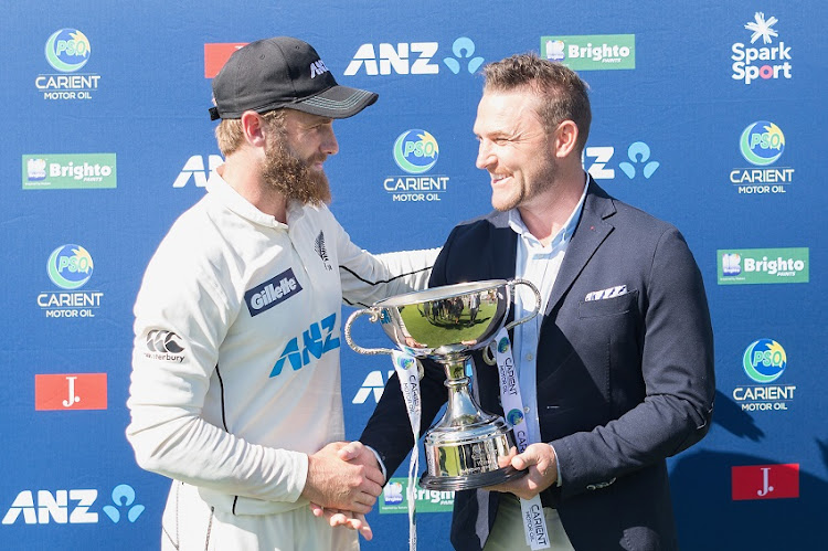 Captain Kane Williamson of New Zealand (L) receives the trophy from former Blackcaps captain Brendon McCullum after the series win on day four of the Second Test match in the series between New Zealand and Pakistan at Hagley Oval on January 06, 2021 in Christchurch, New Zealand.