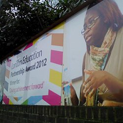 a large digitally printed sign with a lady on it talking that says; london education 2012