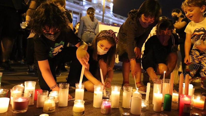 Niños encienden velas en recuerdo de las dos niñas.