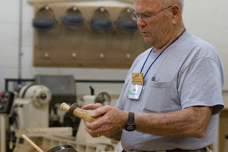 Photo: Bob shows a jig to hold napkin rings with a wedge he inserts to keep it tight.