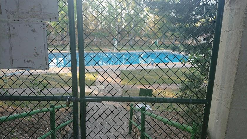 Entrada de la piscina con un candado en la puerta.