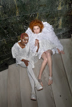 Photograph of me with short pink hair, wearing white lace facial decals, ornate ruffled and ruched white dress. I am holding hands with a similarly dressed pale skinned, ginger haired model, and we are sitting on a marble staircase