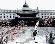man met raket op de rug op een plein met getekende hofdames en bloeiende boompjes. Op achtergrond een Koreaanse tempel en daarachter 19e eeuwse bebouwing