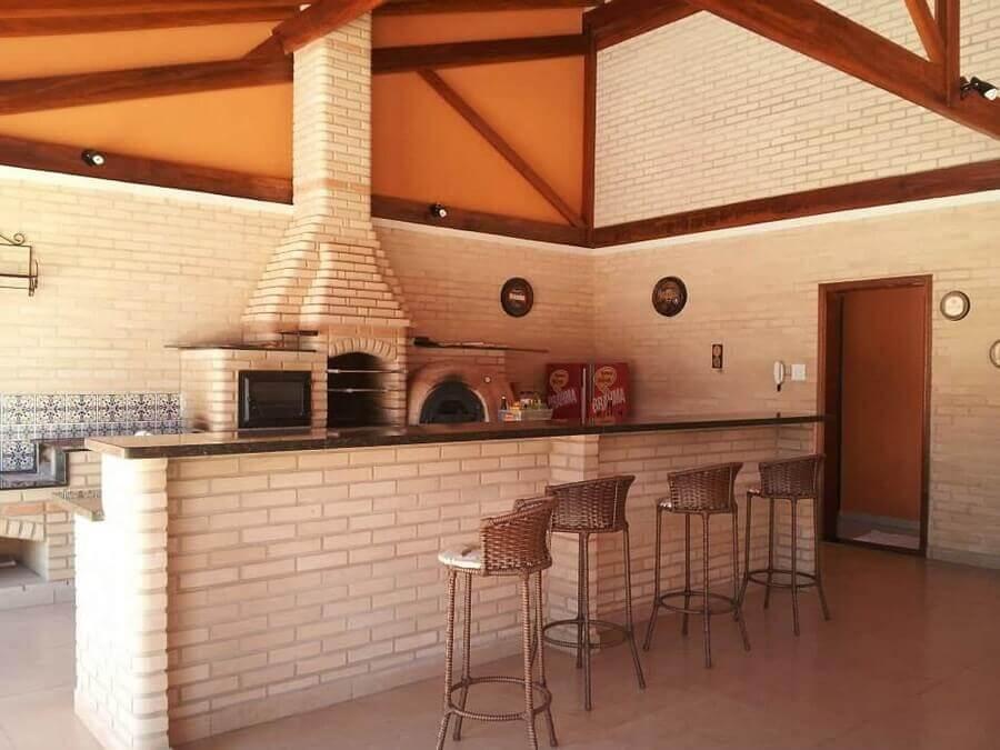 Área externa de chácara com tijolinhos revestindo churrasqueia, forno, paredes e bancada, piso de cimento queimado e bancos marrom,