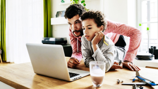 image of man helping boy with laptop