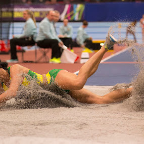 World Champs long jump.  by Ron Russell - Sports & Fitness Running ( jumping, female, length, sand splash, running )