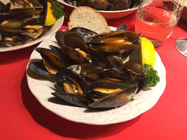 Steamed Mussels In A Bowl Along With A Lemon Wedge And A Slice Of Bread.