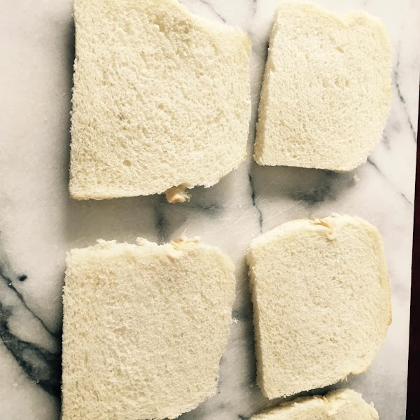 Roll each piece of bread with a rolling pin to flatten them out. I...