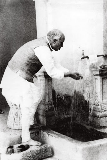 Jawaharlal Nehru washing his hands at Anand Bhavan, Allahabad after lunch at a congress working committee meeting