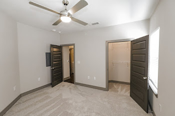 B3 floorplan spacious bedroom with dark gray doors, plush carpet, and a ceiling fan