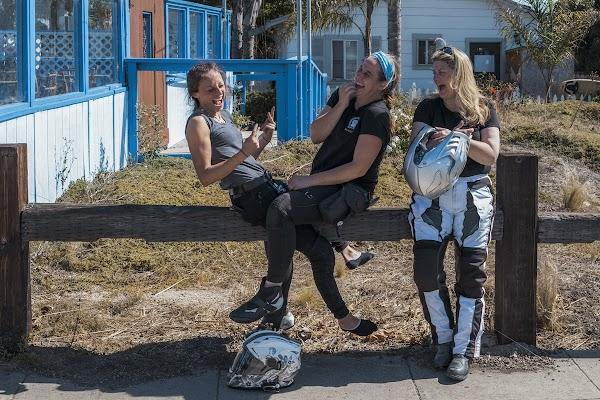 Três mulheres conversando e sorrindo.