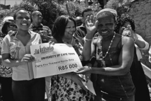 EXCITED: Top matriculant Mandisa Nene receives a cheque from Noluthando Mayende-Sibiya while her mother Sibongile looks on. Pic. Thuli Dlamini. 14/01/2010. © Sowetan.