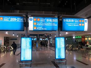 Photo: L'un des nombreux panneaux indiquant les différents secteurs de portes d'embarquement et dessous le plan du hall central avec l'indication du temps à parcourir pour aller d'un endroit à l'autre