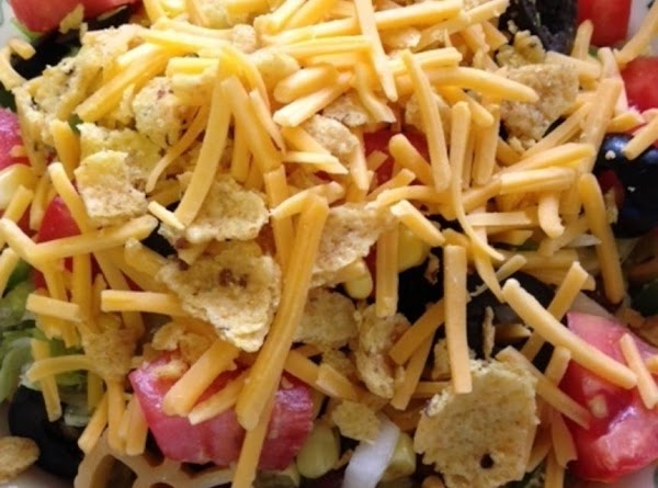 Top with crumbled Fritos and shredded cheese.