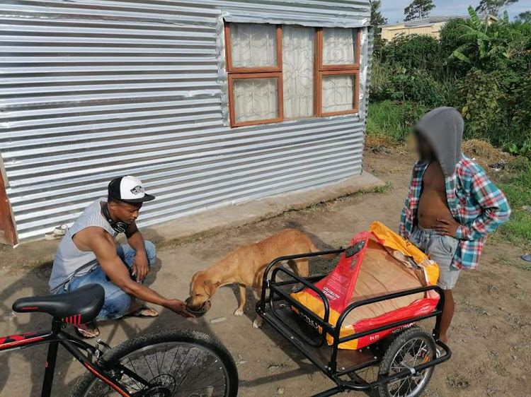 Ben Rexana, left, feeds a neglected dog in Mdantsane with the help of one of his dance students.