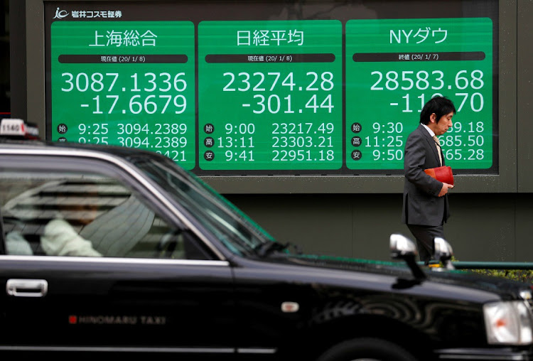 A man walks past an electronic display showing Asian markets indices outside a brokerage in Tokyo. Picture: REUTERS
