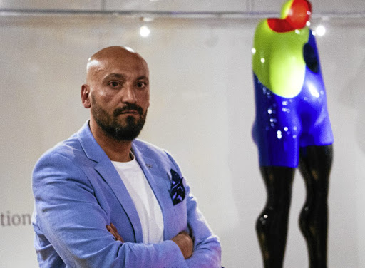 Slick finish: Sam Shendi poses at Graham's Fine Art Gallery alongside a work from his Giant collection. These large imposing resin sculptures represent different stages of depression the artist went through after abuse.  Picture: SUPPLIED
