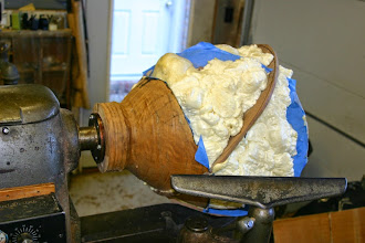 "Photo: Here's what it looked like in process.  It's a natural-edge maple vessel that incorporates two intersecting walnut ""orbital"" rings of different diameters at different orientations. He described the process for turning the bowl, slicing it in different planes, reassembly with the rings incorporated in the glue-up,  and filling it with construction foam to provide support for hollow turning the composite."