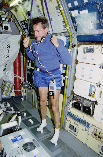 Linnehan exercises with a bungee strap in the Spacelab module