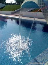 Photo: Piscina transbordante construída em Betão Armado e revestida a pastilha de cor azul celeste. Esta piscina contempla aproximadamente 13,5 x 5,5mts e de 1 a 2,70mts de fundo. Os equipamentos de que esta dispoem são os seguintes: um filtro Cantabric Astralpool 750mm, uma bomba Astralpool Glass Plus 2CV TRIF., um quadro electrico c/ transformador e comandos de manobra de fácil acesso, uma bomba supradora de ar para sistema de hidromassagem, um sistema de desinfecção e controle da qualidade da água composto por um equipamento de desinfecção através de raios UV, complementado com um doseador de cloro em pastilhas e uma bomba doseadora e controladora de pH, tudo marca CTX, três projectores extra-planos de Led´s multicolor da Astralpool, com receptor e comando à distância, uma bomba de calor para aquecimento da água modelo 500TI-REV TRIF., da marca americana AIR ENERGY, uma manta exotérmica de bolhas e o respectivo enrolador com rodas, uma cortina/cascata de àgua em AISI 316 Polido da marca Astralpool, entre outros.