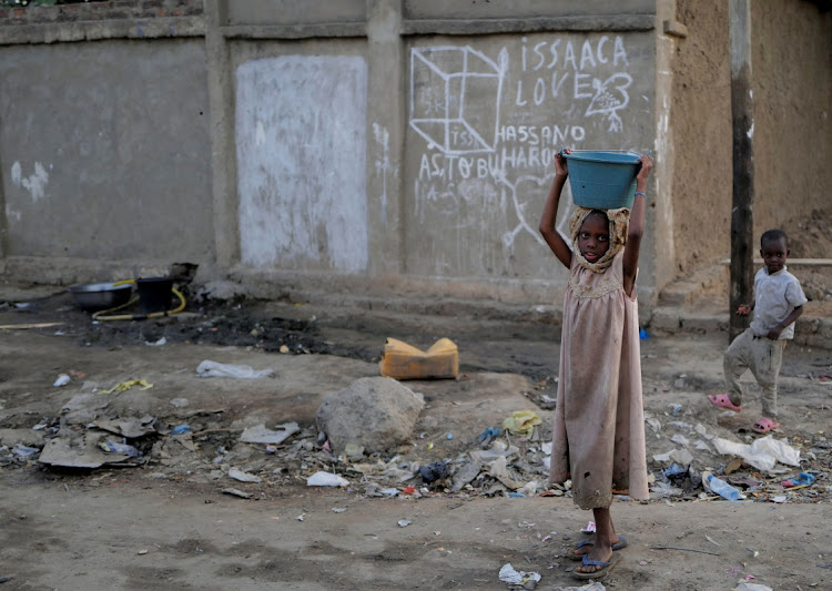 "A girl carries a basin in a poor neighbourhood, as rebels in northern Chad are ready to observe a ceasefire and to discuss a ""political settlement"" after the battlefield death of President Idriss Deby last week in N'djamena, Chad on April 25, 2021."