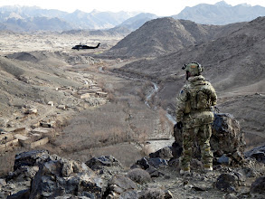 Photo: A Special Forces Reservist observes a valley in Chenartu, Uruzgan as a Blackhawk circles above. Mid Caption: SOTG XIV, based on a company group drawn from Army Reservists of the 1st Commando Regiment, partnered with the Provincial Response Company Uruzgan (PRC-U) in operations to support the Afghan government, shield the local population and disrupt the insurgency in the southern provinces. Continued effort in Uruzgan and Kandahar over the winter months has led to the removal of prominent insurgent members and the recovery of several hidden weapons caches, including stores of Improvised Explosive Device (IED) components that would have otherwise been used to target ISAF forces and Afghan civilians.Deep: The Special Operations Task Group is deployed to southern Afghanistan to conduct population-centric, security and counter network operations. SOTG support the Afghan National Police's Provincial Response Company in Uruzgan and northern Kandahar. SOTG includes members from the Special Air Service Regiment (SASR), 1st and 2nd Commando Regiments, the Incident Response Regiment, Special Operations Logistic Squadron and supporting units.