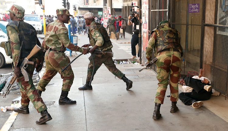 Soldiers beat a supporter of the opposition Movement for Democratic Change outside the party's headquarters in Harare, Zimbabwe, August 1 2018. Picture: REUTERS/MIKE HUTCHINGS