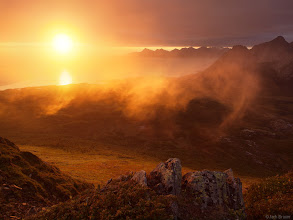 Photo: At the end of a dreary overcast day the sun shines a fiery sunset through a gap under the clouds. The famous Strandatindan, or Stranda peak, rises up on the right side of the photo. As seen from Blåfjellet, a small mountain near the village of Kjerringøy which is north of Bodø.