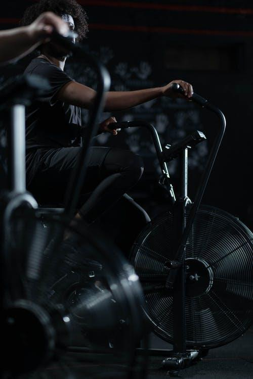 Person in Black Activewear Using a Stationary Bicycle