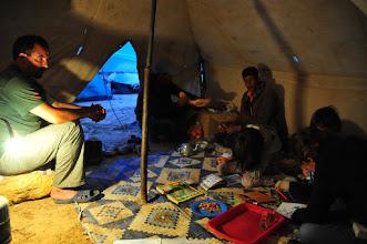 Photo: Bivouac - pendant que notre guide Mohammed (à gauche) nous fait la cuisine, assisté du chamelier (au centre) on dessine et on lit des histoires. La pluie tombe tout autour.