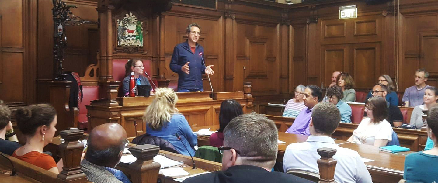 George Monbiot speaking to an audience of Rebels, Youth, and Trade Unionists, in a wood-panelled room in Oxford Town Hall.
