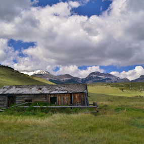 Cut Across Cabin by Don Evjen - Buildings & Architecture Decaying & Abandoned ( clouds, cabin, mountains, grass, green, montana, blue skies, spring, rustic )