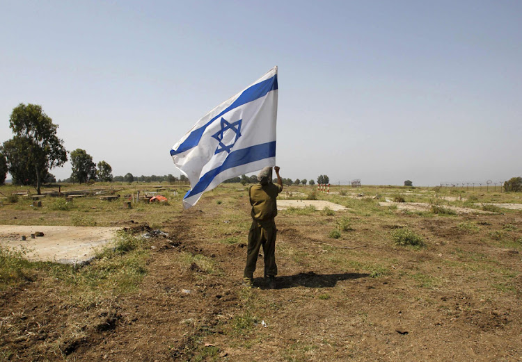 An Israeli soldier places a flag near the Golan Heights.  Picture: REUTERS