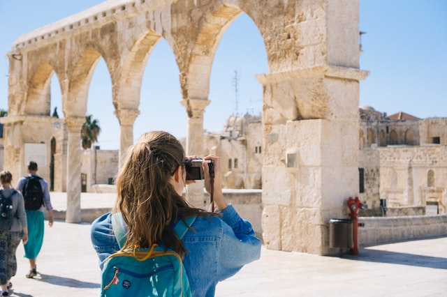 A woman taking a photo of the Acropolis