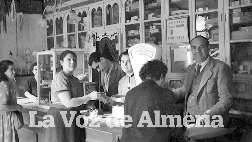 Julio Castellón, con traje, chaleco y corbata, detrás del mostrador. A su lado está su hija Adela.
