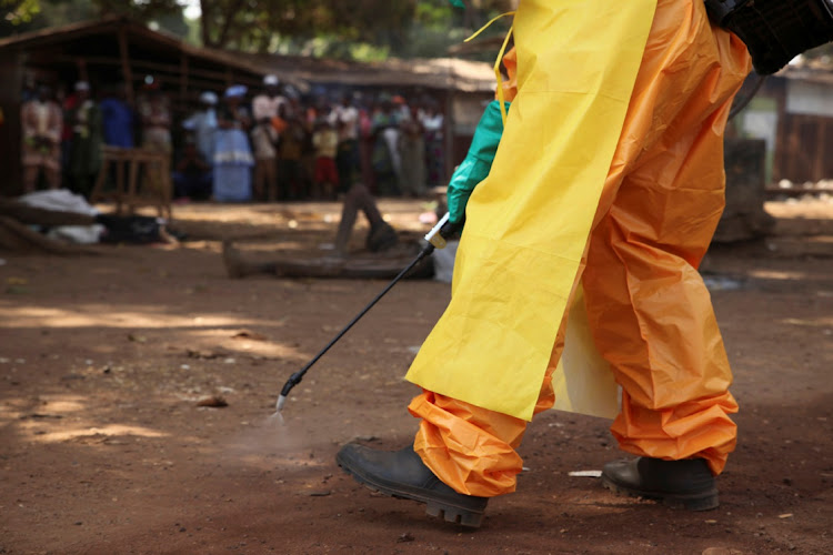 A member of the French Red Cross disinfects the area around a motionless person suspected of carrying the Ebola virus as a crowd gathers in Forecariah, Guinea on January 30, 2015.