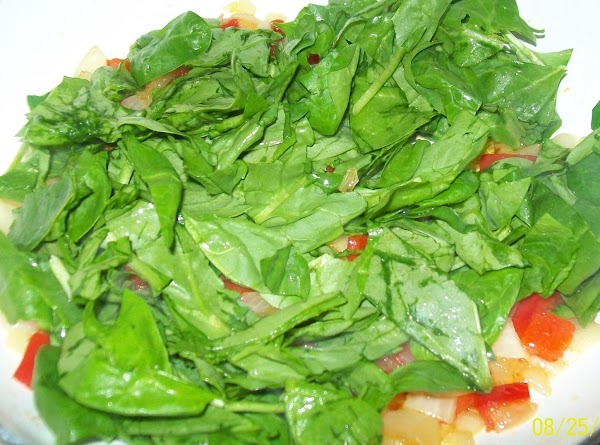 Add a good helping of fresh ground pepper and the spinach to the onions...