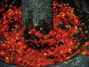 Photo: pounding softened soaked dried red chillies to make dipping sauce for grilled chicken