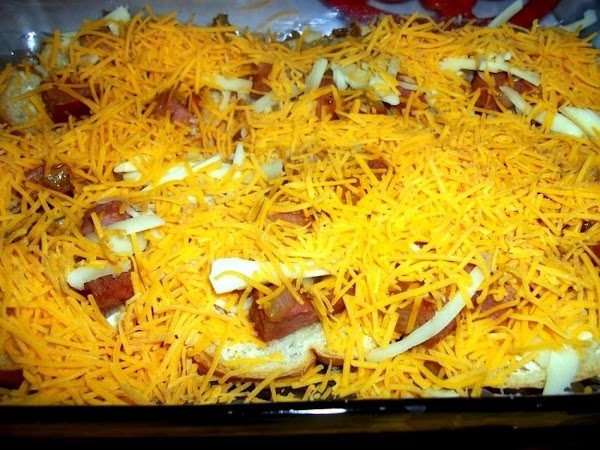 Sprinkle half the cheeses over the ham. Then, layer with another row of bread.  Sprinkle...
