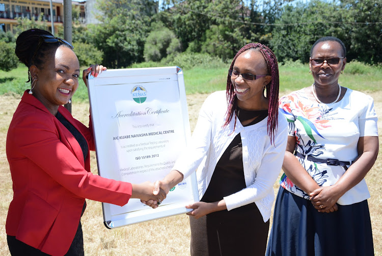Kenya Accreditation Services assistant director in charge of safety and health Dorris Mweni hands over an accreditation certificate to the director in charge of clinical services at AIC Kijabe Hospital Ivylene Wanjiru at the facility's Naivasha branch on Monday, February 10, 2020