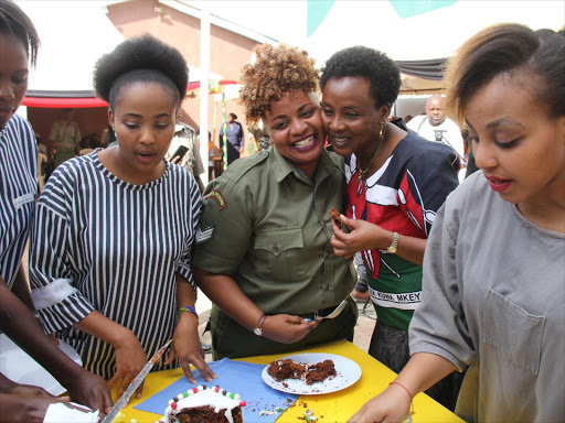 Deputy Chief Justice Philomena Mwilu joins inmates and staff at Lang'ata Women Prison in eating a cake to mark Madaraka day celebrations