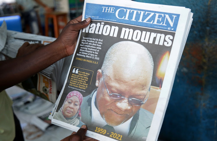 A man holds a newspapers after the death of Tanzania's President John Magufuli in Dar es Salaam.