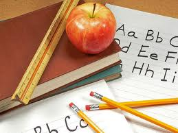 image of apple, books, paper, ruler and pencils on a desk
