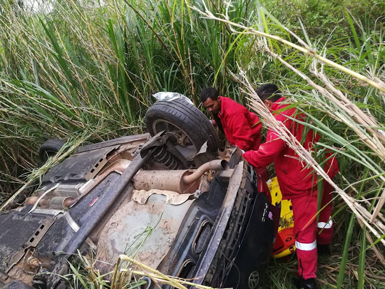 Medics attend to an injured man at the wreckage of his car in a sugarcane field near Stanger, north of Durban, on Wednesday.