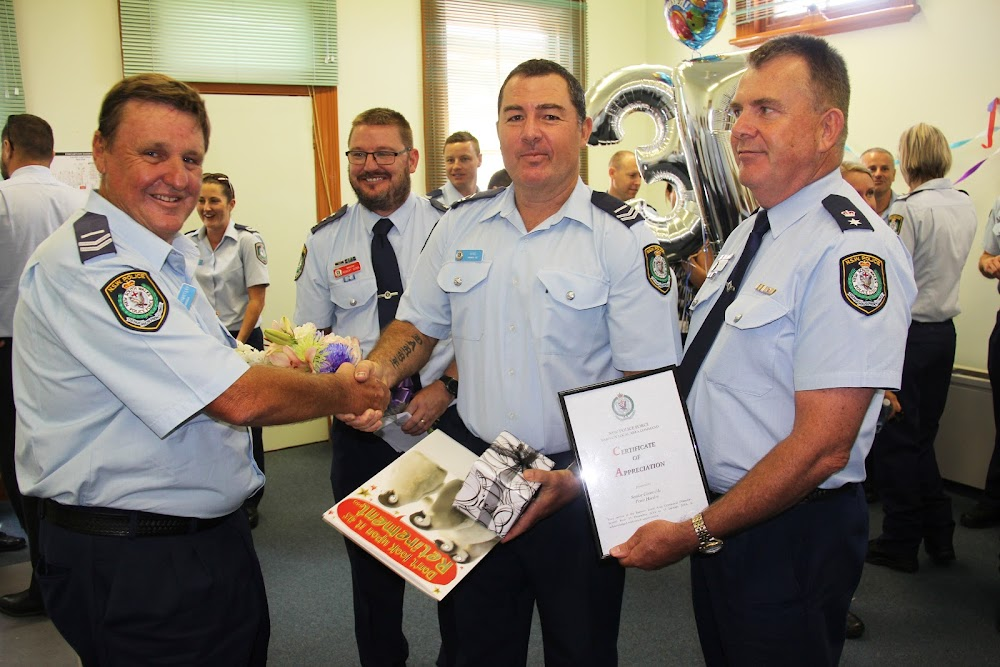 Senior Constable Peter Hartley receives parting gifts from fellow Narrabri officer Senior Constable Ben King and acting Barwon Local Area Commander Superintendent Fred Trench, as officer in charge of the station Inspector Robert Dunn watches on.