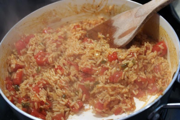 Rice and tomatoes cooking in a skillet.